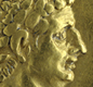This Roman gold coin shows the Emperor Claudius, with war trophies. The Latin letters stand for 'Triumph over the Britons'.