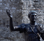 A statue of the Emperor Trajan, in front of the remains of London�s Roman wall.