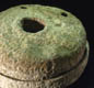 A quern stone, for grinding grain to make flour. You poured grain in at the top, used a wooden handle to turn the top stone, and collected the flour ground between the stones.