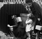 A family entering an Anderson shelter, carrying their gas masks in boxes.