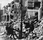 A photo of a bomb-damaged street, 1943. The boys have made a swing from ropes tied to a lamp post. 