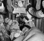 Christmas in an air raid shelter - a young girl sleeps under decorations and stockings in 1940.