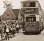 Children being evacuated.  A group of double decker buses await them.