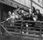 Children waving goodbye from a ship's gangway as they prepare to travel to Canada.