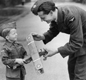 Everyone was asked to save scrap metal. This boy was  offering his toy plane to an airman.  Do you think this was a specially staged photo?