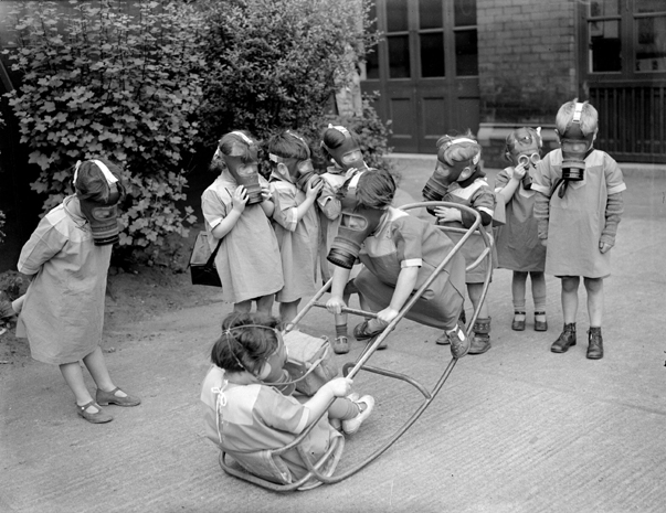 Nursery school children at play wearing their gas masks this photo