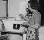 This woman used a small tin bath to store water. In her kitchen in Northampton, you can see a gas cooker (left) and a boiler (centre) for washing clothes.