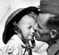 A soldier kissing his daughter (who is wearing a tin helmet and carrying a gas mask).